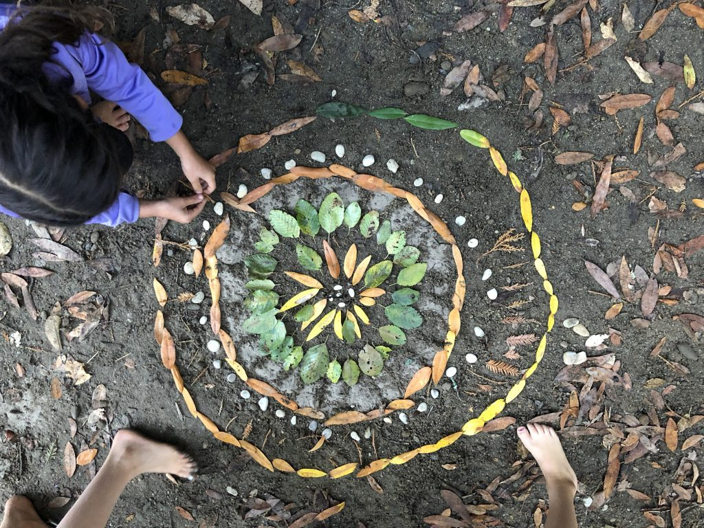 photo of youth creating nature artwork on forest floor