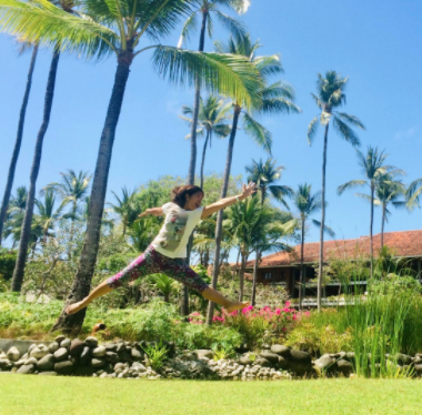 photo of cherry jumping on green lawn with palm trees in background
