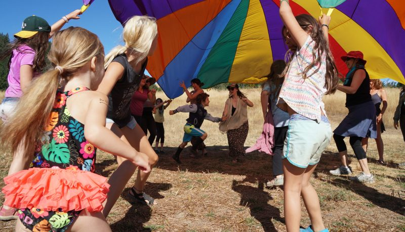 photo of youth playing under a rainbow parachute