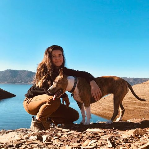 portrait of guide Sabrina with dog and lake in background