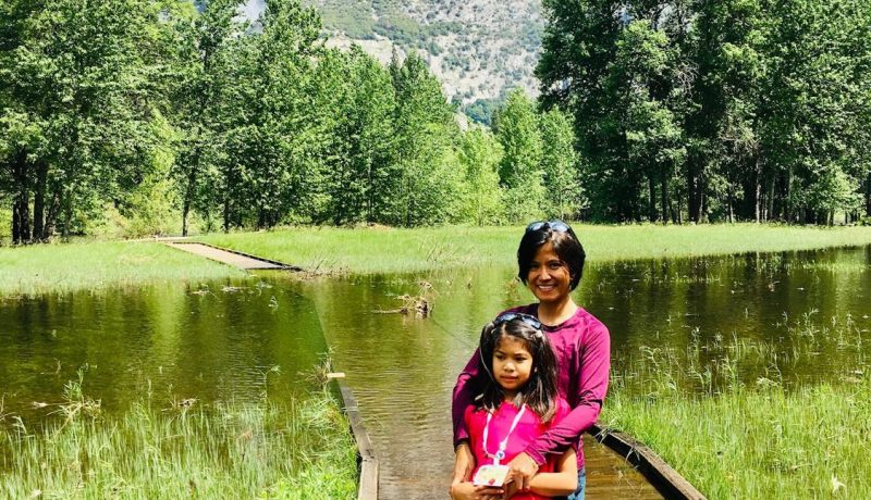 Board member Cherry with child on a dock in front of large mountain with waterfall