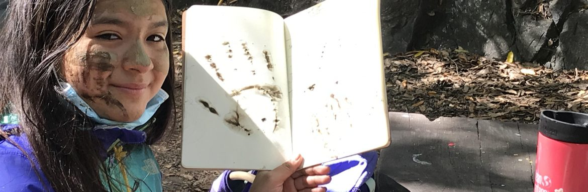 youth with mud painted face showing muddy handprints in notebook