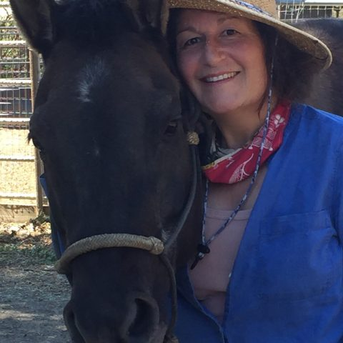 Gaia Passages' Board Member Amena smiling with horse