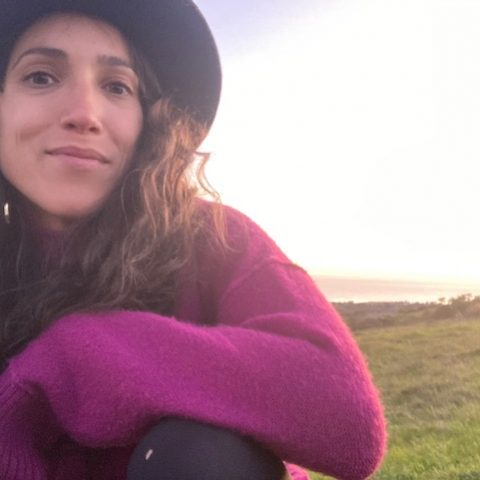 Photo of guide Angela in purple sweater with grassy landscape behind